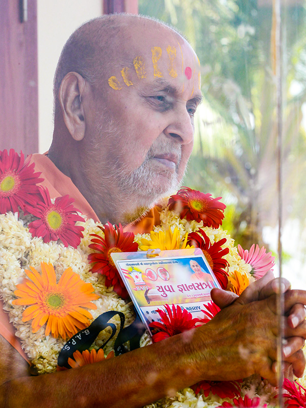 Swamishri sanctifying an identity card for the 'Yuva Jnansatra'