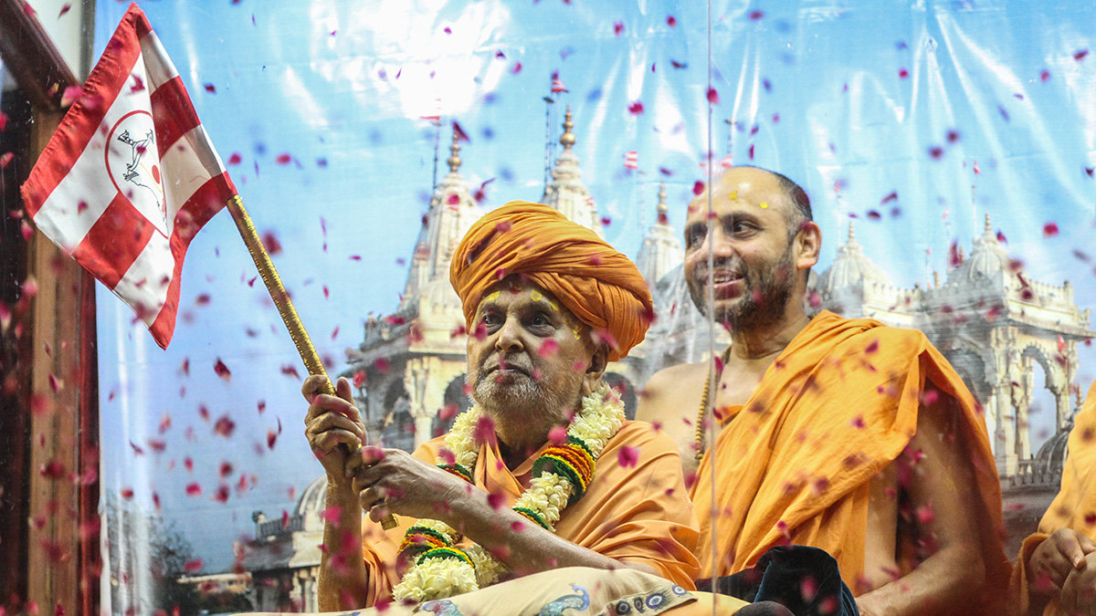 Swamishri waves the BAPS flag while flower petals are showered on the sadhus and devotees below
