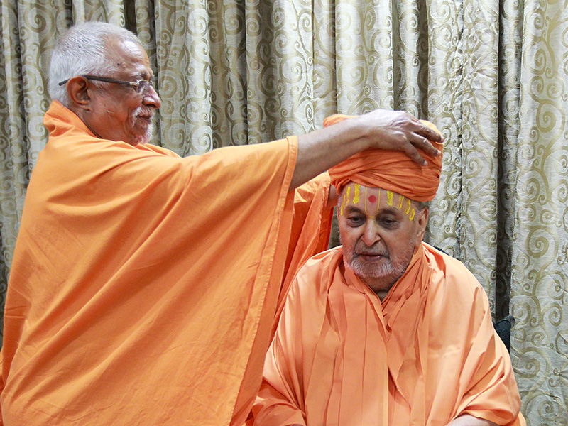 Pujya Doctor Swami ties a pagh in traditional style on Swamishri, as part of the celebrations for 'Pramukh Varni Din'