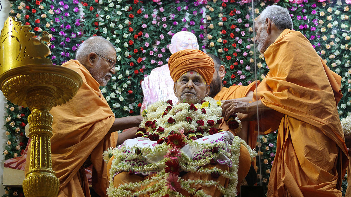 Pujya Kothari Swami and Pujya Mahant Swami honor Swamishri with a shawl of flowers