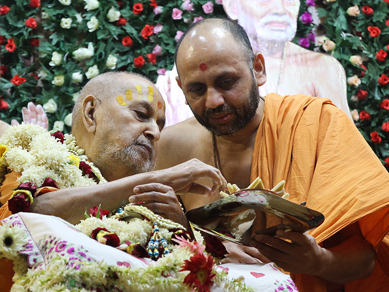 Swamishri sanctifies sweets for devotees