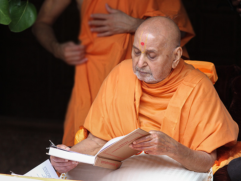 Swamishri reads from a Sanskrit textbook