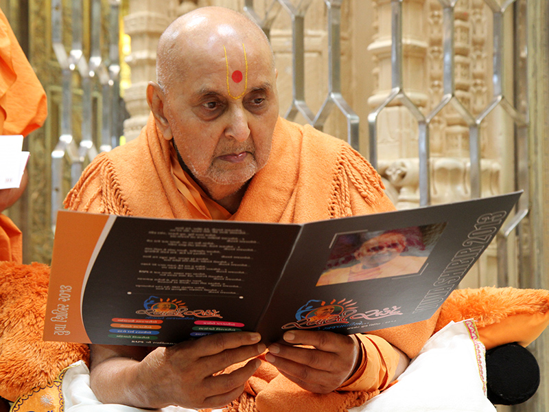 Swamishri sanctifies a shibir brochure