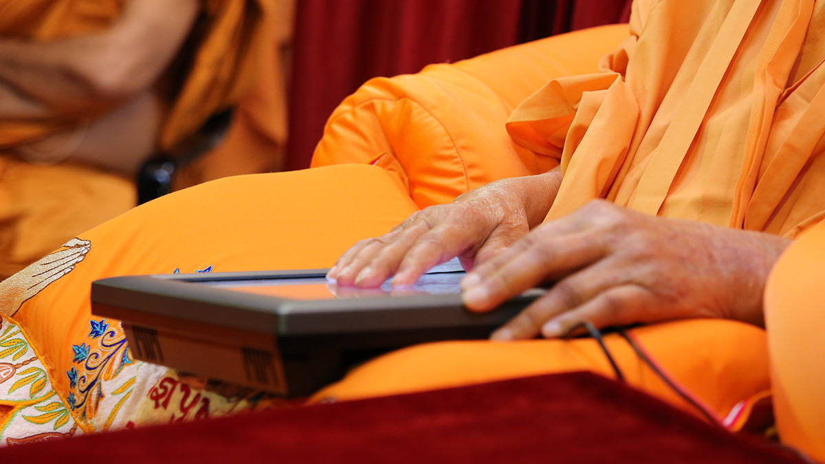 Swamishri operates a touchpad remote to serve dudhpak to sadhus
