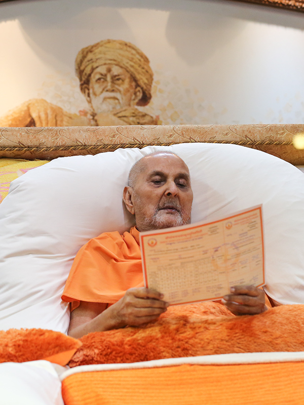 Swamishri sanctifies the marksheets of Pujya Gnanvardhan Swami and Pujya Paramvivek Swami, awarded the degrees of Swaminarayan Vedantacharya (M.A.) by Somnath Sanskrit University, India