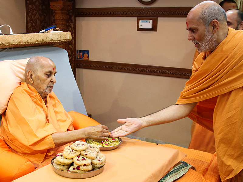 On the occasion of Dussehra, Swamishri blesses Pujya Viveksagar Swami with sanctified jalebis