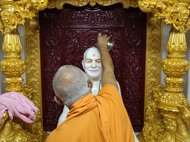 Senior sadhus perform abhishek of the newly consecrated murti of Brahmaswarup Yogiji Maharaj