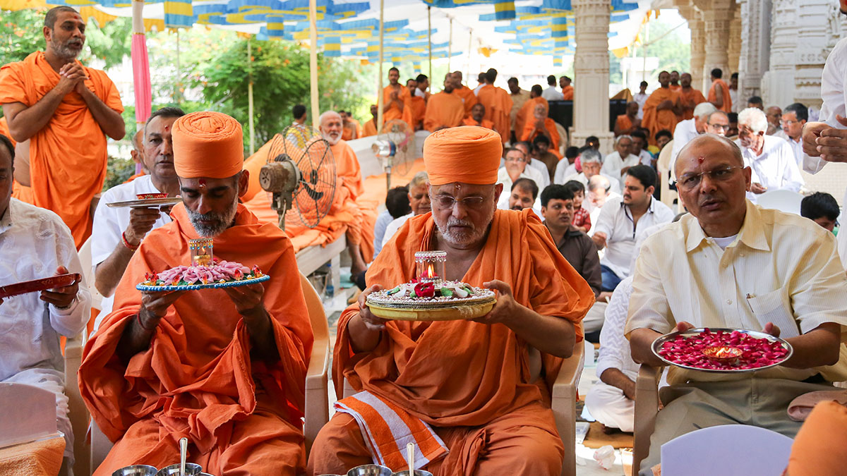 Pujya Ishwarcharan Swami and Pujya Anandswarup Swami perform mahapuja arti with devotees