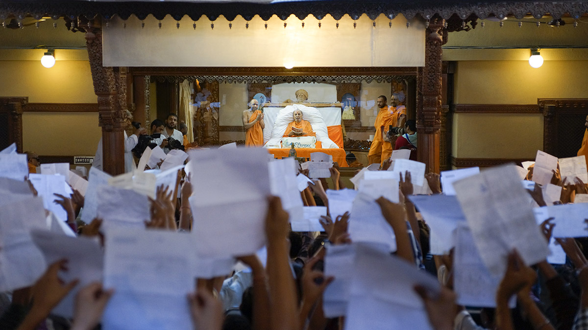 Swaminarayan Vidyamandir students show their marksheets to Swamishri