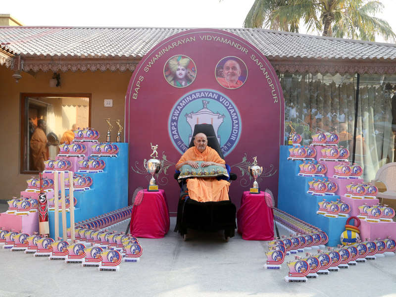 HH Pramukh Swami Maharaj with trophies and awards for the students of Swaminarayan Vidyamandir, Sarangpur