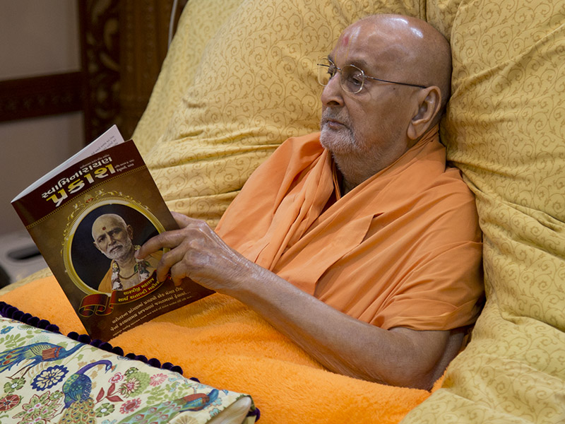 Swamishri reads the latest issue of Swaminarayan Prakash commemorating the 'Shaardh Shatabdi Mahotsav' (150 years) of Brahmaswarup Shastriji Maharaj