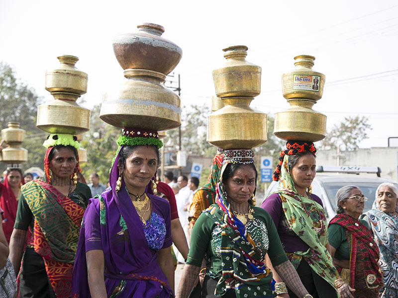 Women carrying water pots participate in the procession
