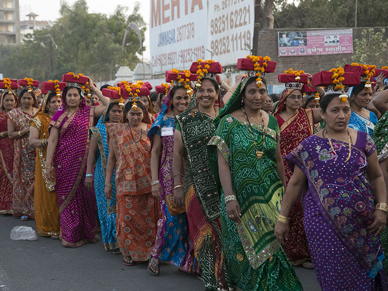 Women carrying 'pothi' (scriptures wrapped in cloth) participate in the procession
