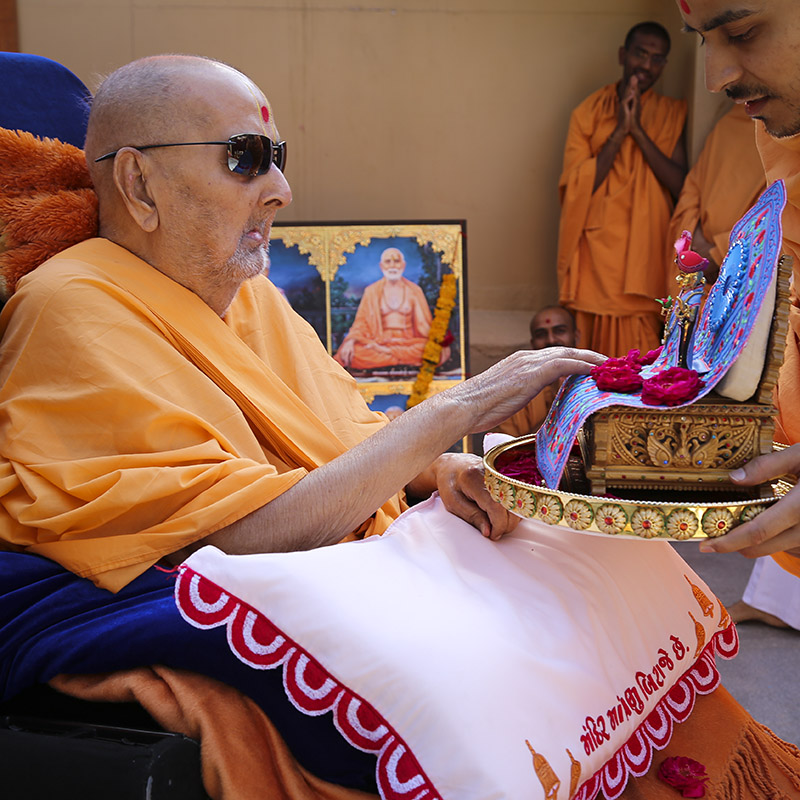 Swamishri touches the feet of Shri Harikrishna Maharaj