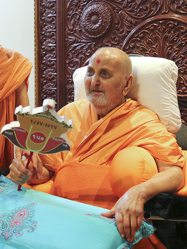 Swamishri waves a chhadi with the symbol for Shastriji Maharaj Saardh Shatabdi Mahotsav
