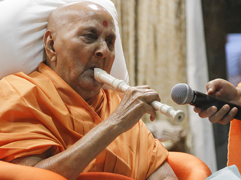 Swamishri plays a flute at night