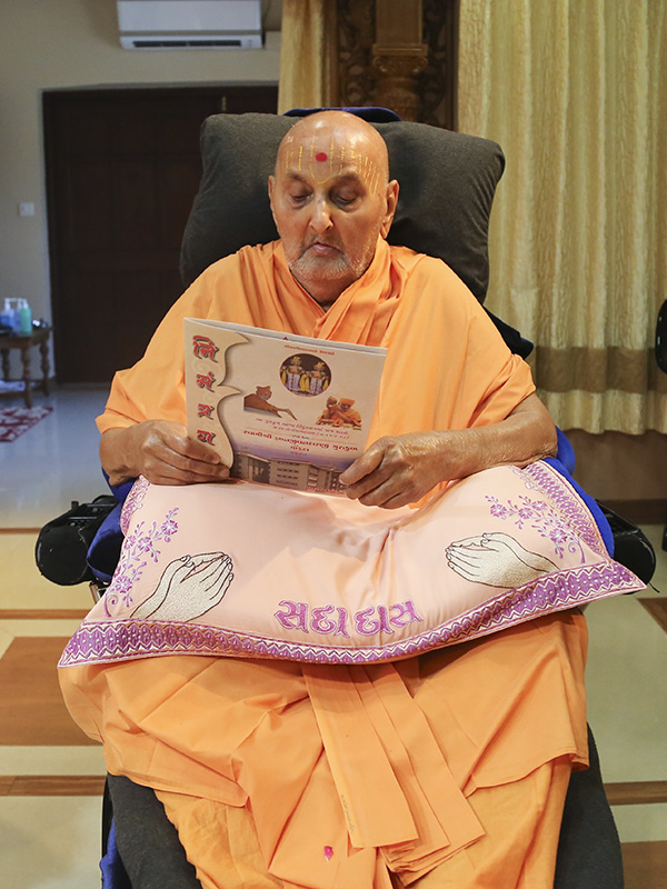Swamishri sanctifies an invitation card from the residential school at Gondal