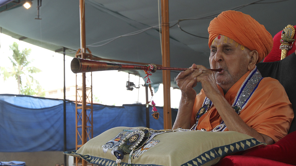 Swamishri blows a traditional musical instrument,  'Bhungal'