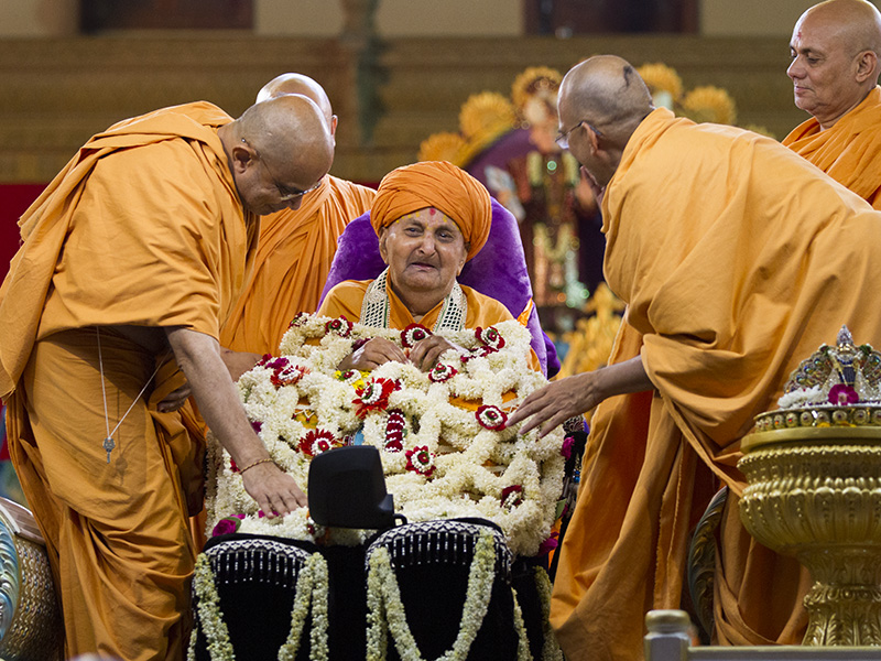 Sadhus honor Swamishri with a shawl of flowers