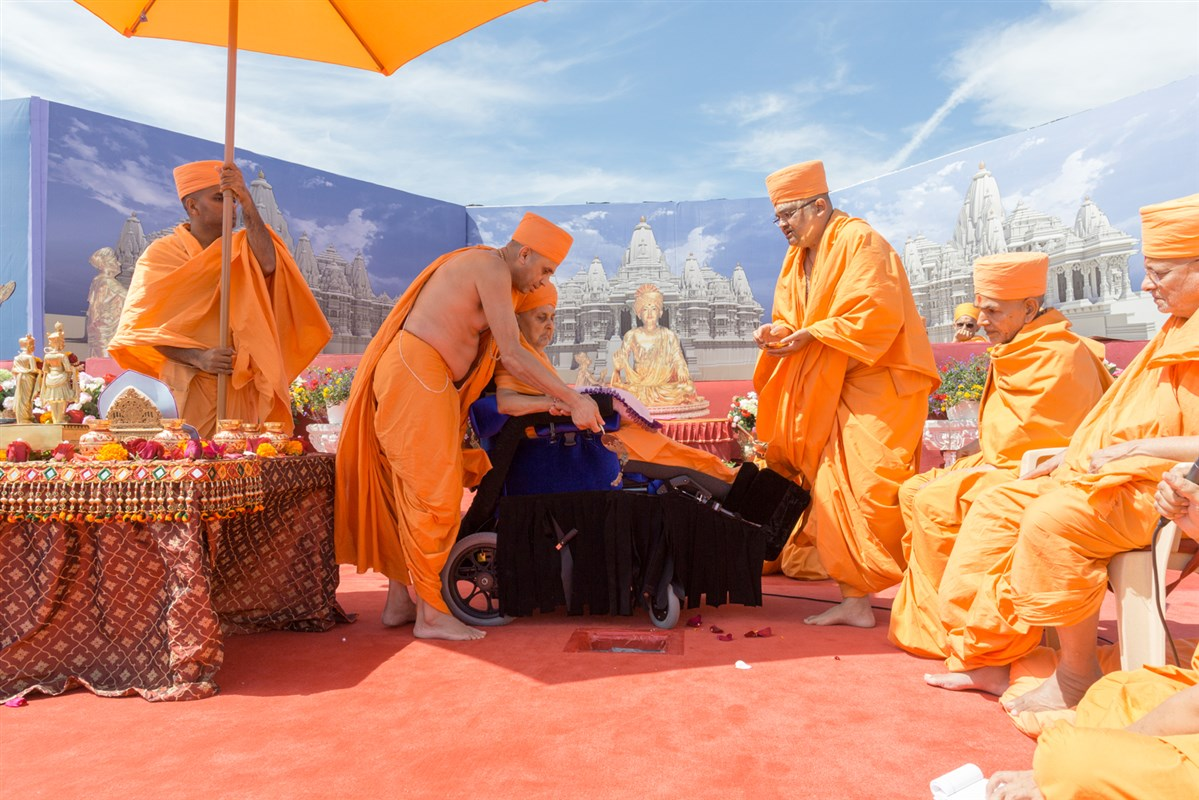 Swamishri pours cement in the main khand, at the pratishtha location of Bhagwan Swaminarayan