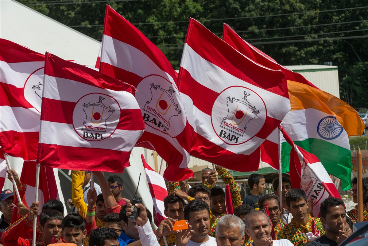 Devotees wave the BAPS flag and Indian national flag on the auspicious occasion