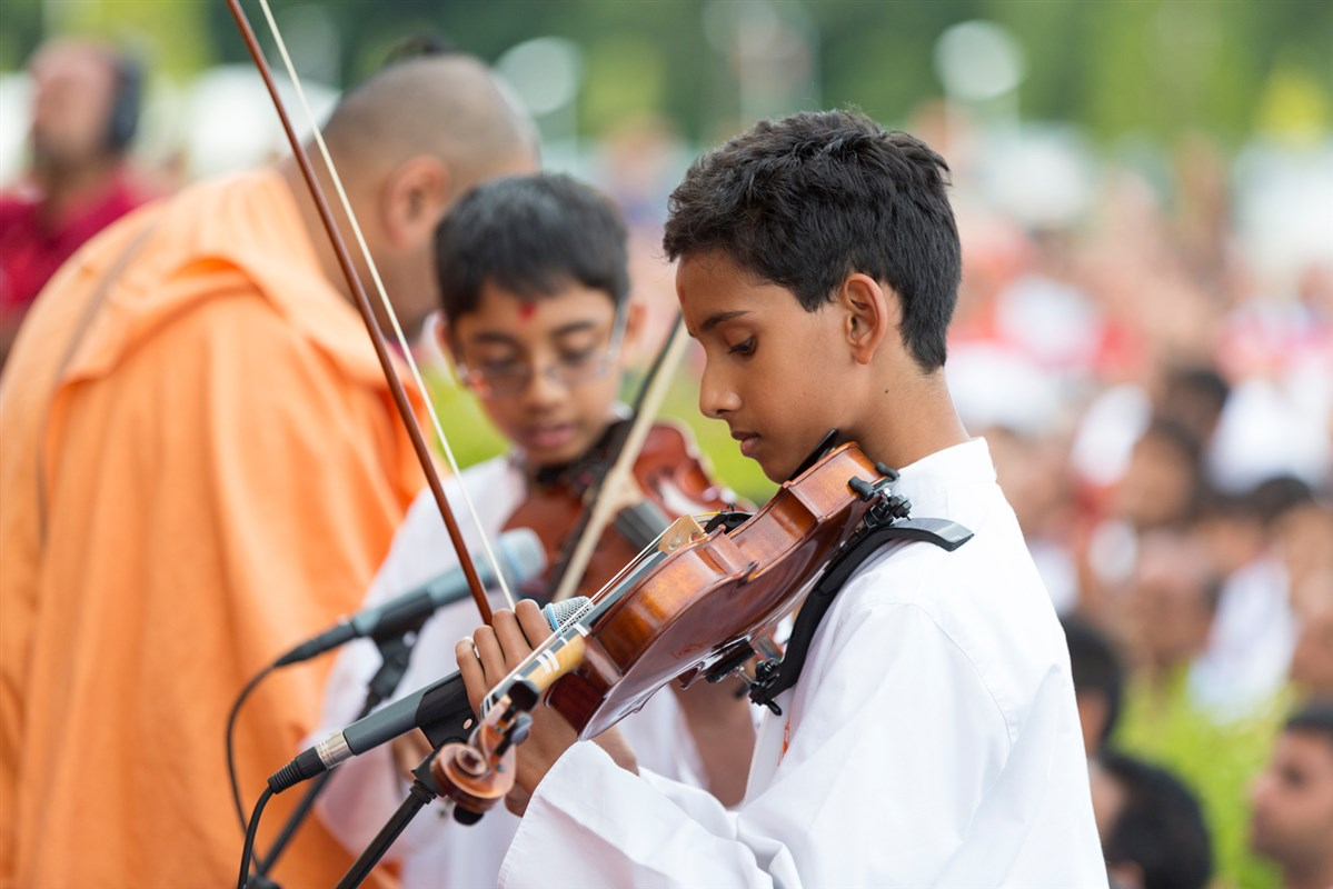 Children play violin in front of Swamishri