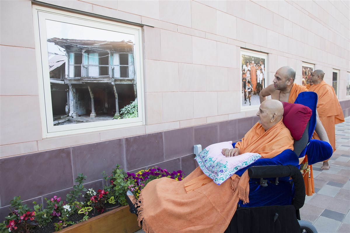 Swamishri observes window screen photographs in the mandir complex