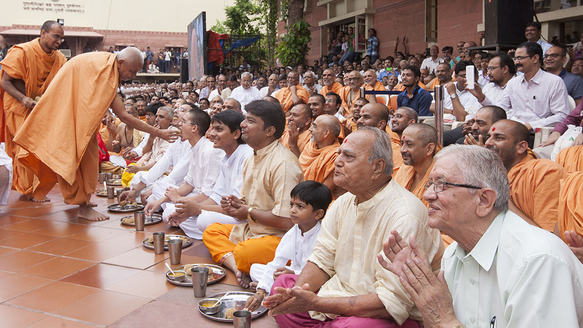 Devotees being served laddus in the presence of Swamishri
