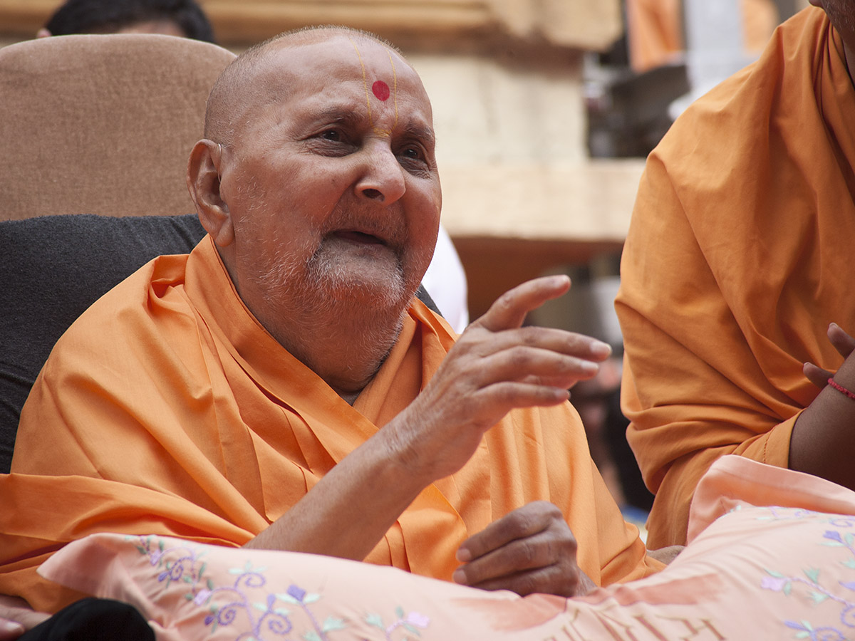 Swamishri in a divine mood while communicating with the deaf devotee