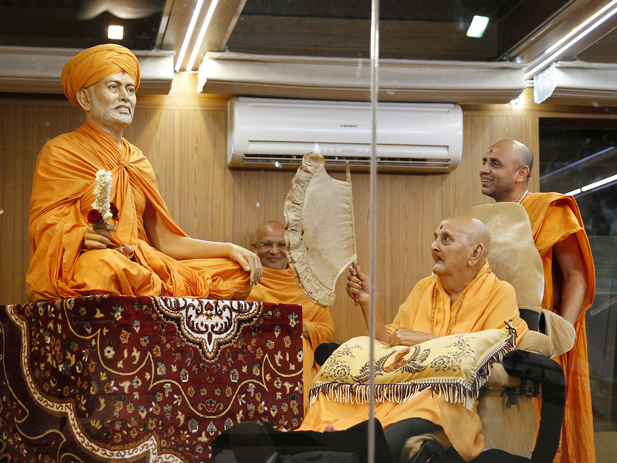 Swamishri reverentially holds a hand fan sanctified by Shastriji Maharaj