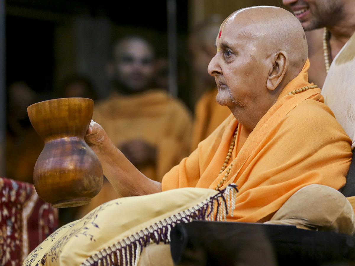 Swamishri reverentially holds a tumbdi used by Shastriji Maharaj