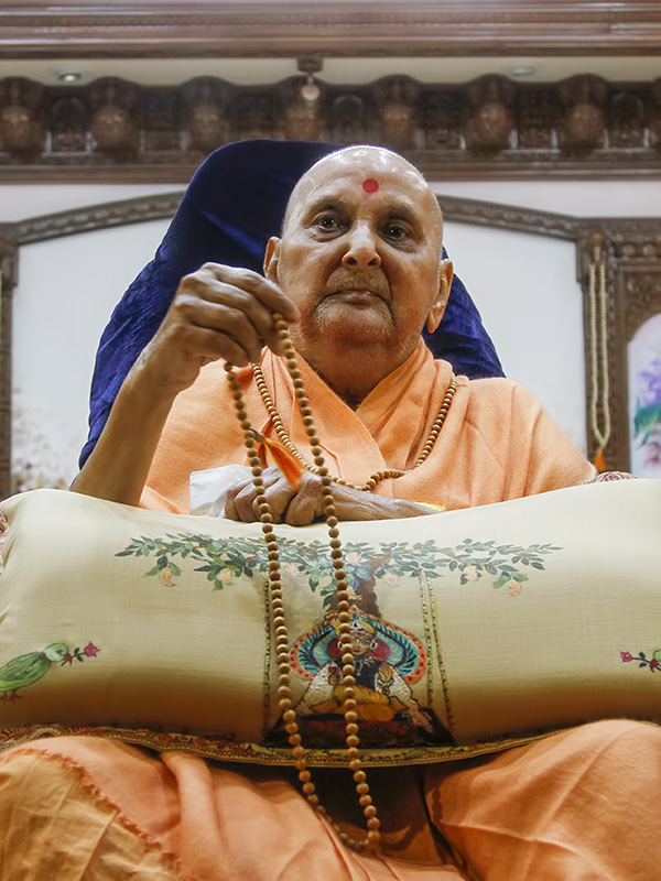 Swamishri doing a mala at night