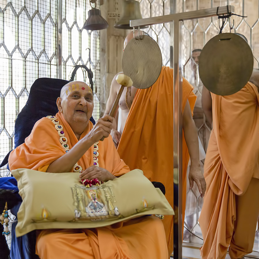 Swamishri plays the jhalar (gong)