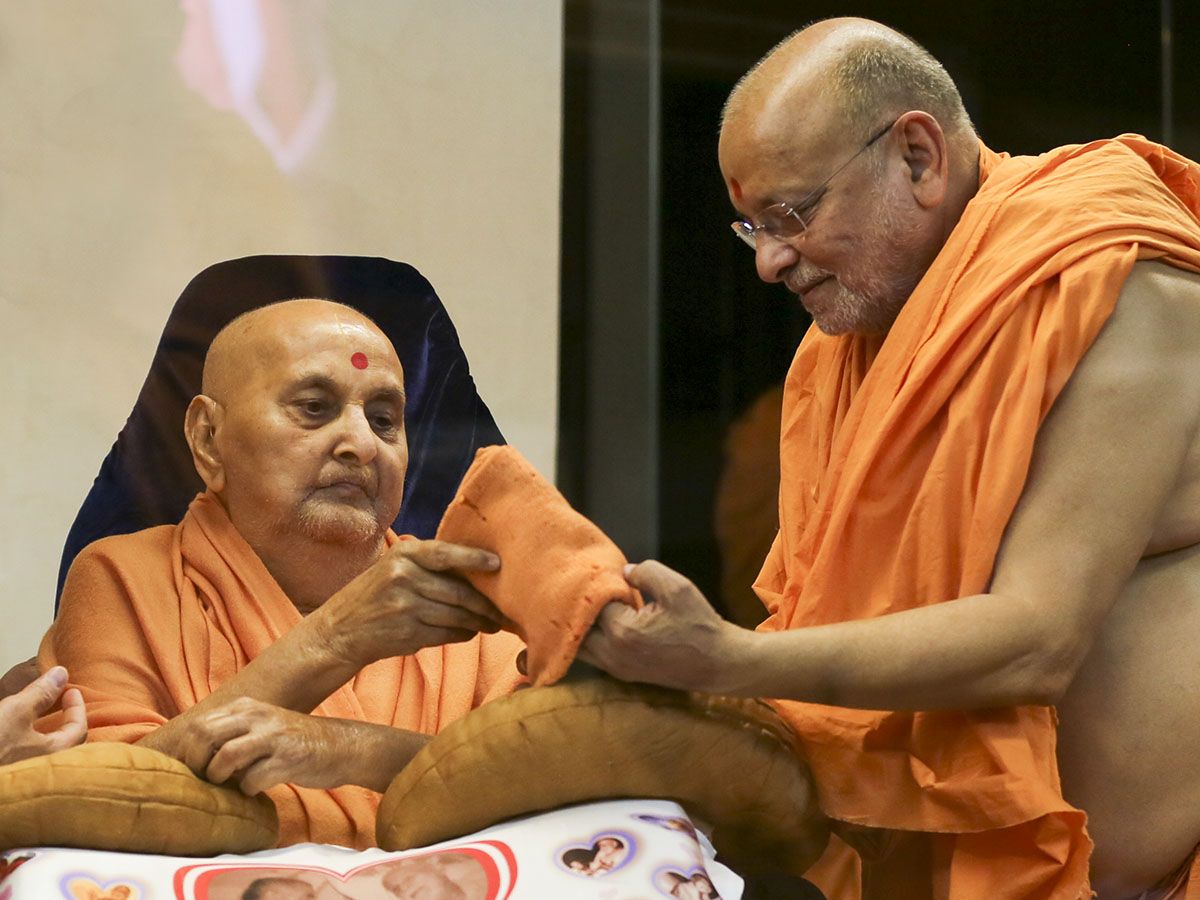 Swamishri reverentially holds a woolen cap worn by Yogiji Maharaj