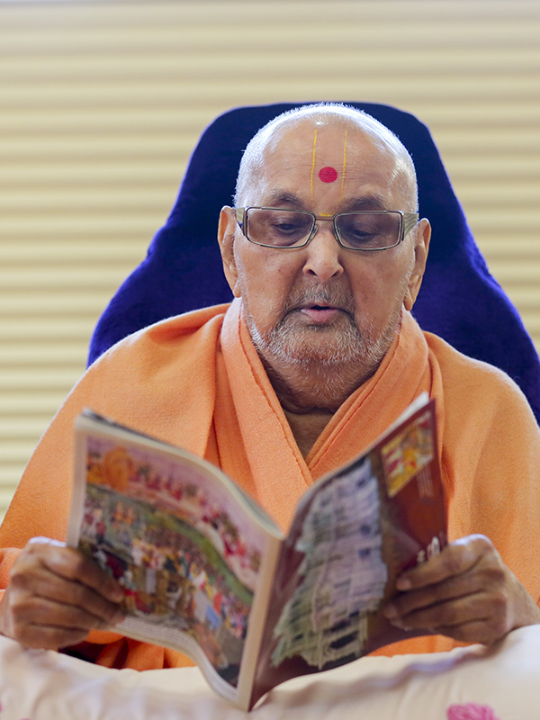 Swamishri reads the latest issue of Swaminarayan Bliss