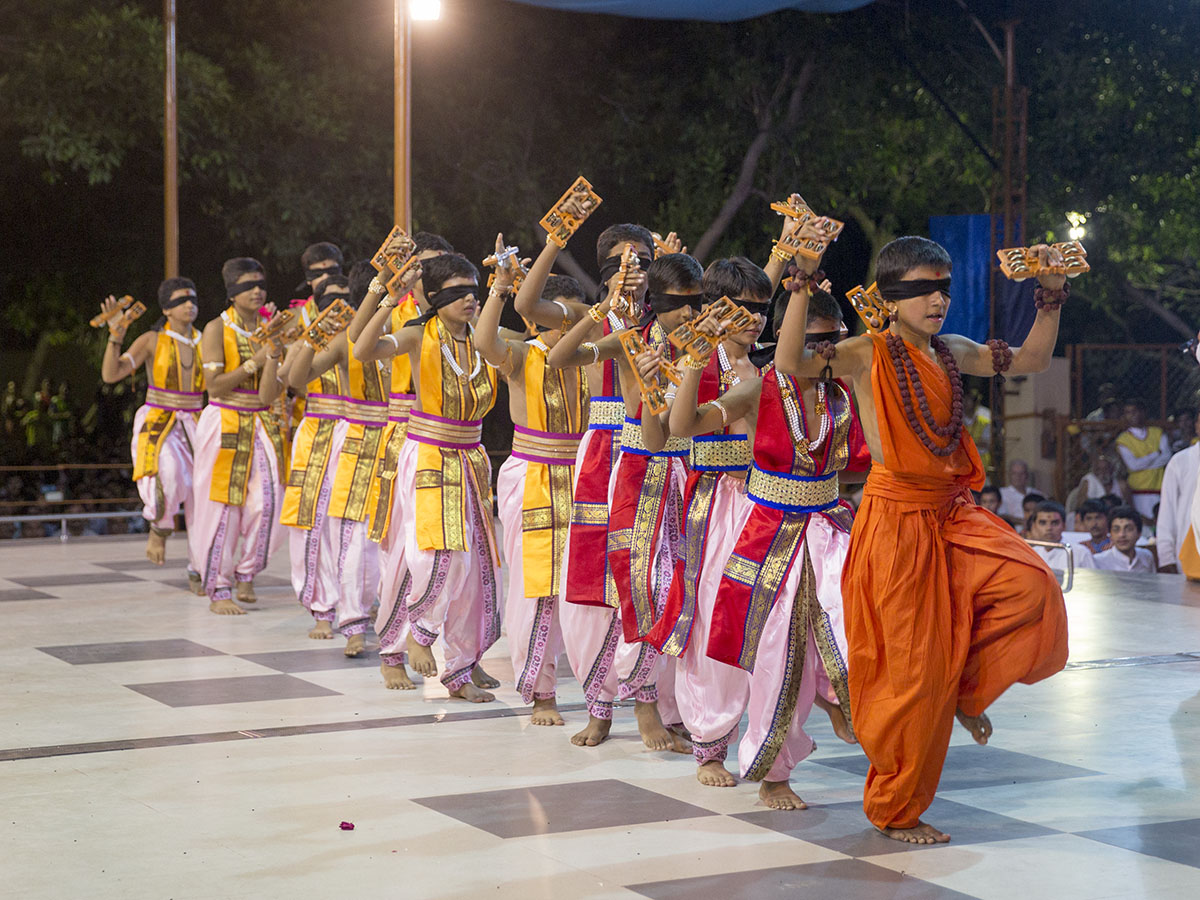 Kids perform a cultural dance while blind folded, before Swamishri