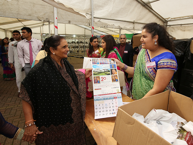 Visitors receive New Year's calendar and prasad