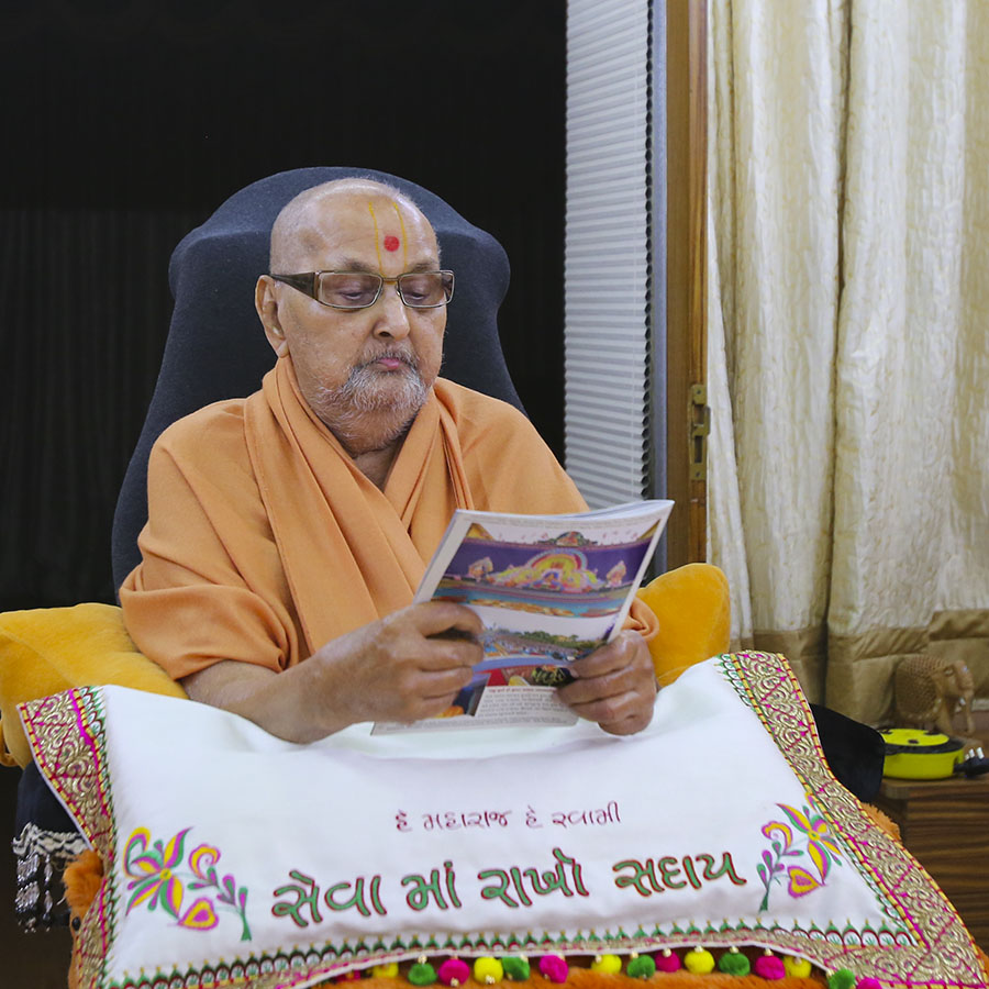 Swamishri reads the latest issue of Swaminarayan Prakash in the evening