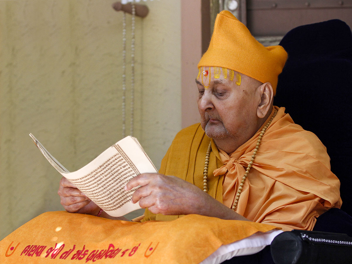 Swamishri reads a scripture at the 'Yagnapurush Vishwavidyalaya'