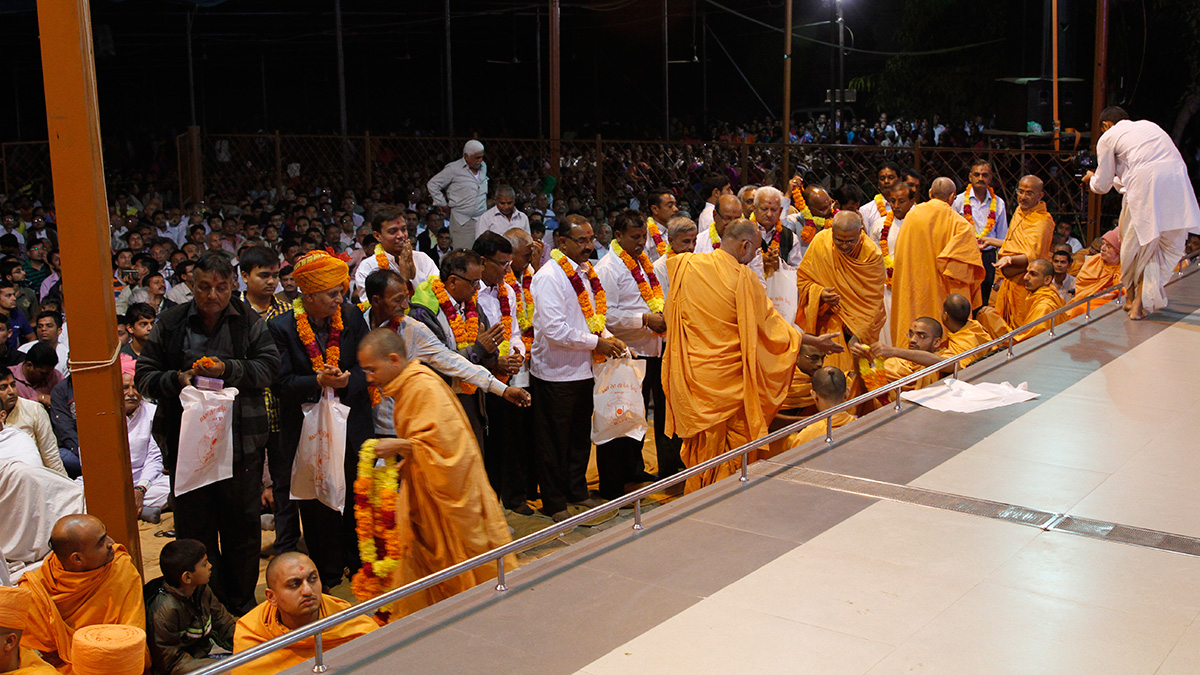 Fathers of the newly initiated sadhus are honored with garlands