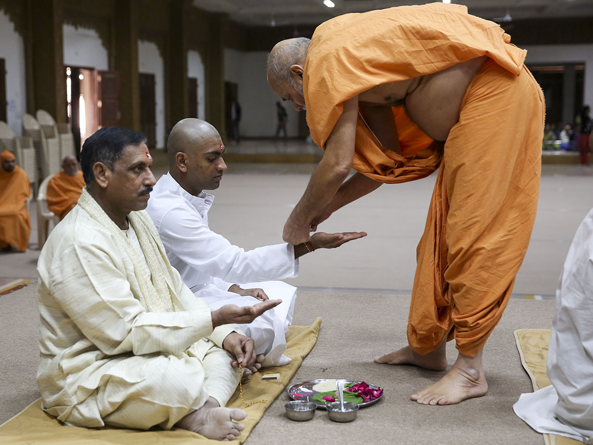 A sadhak and his father participate in the diksha mahapuja