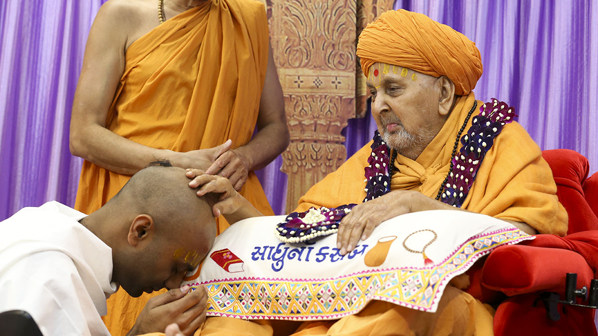Swamishri gives diksha mantra to a newly initiated parshad