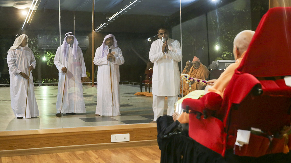 Devotees from the Middle East dressed in traditional Arabic robes pray before Swamishri