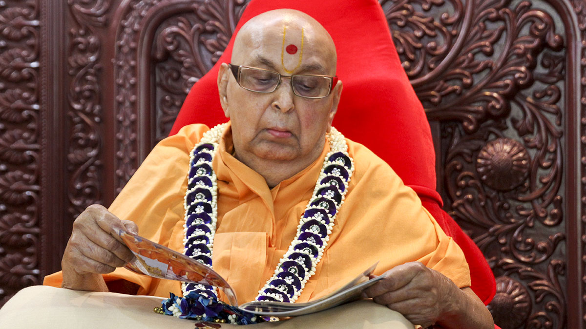 Swamishri reads the latest issue of Swaminarayan Prakash in the morning